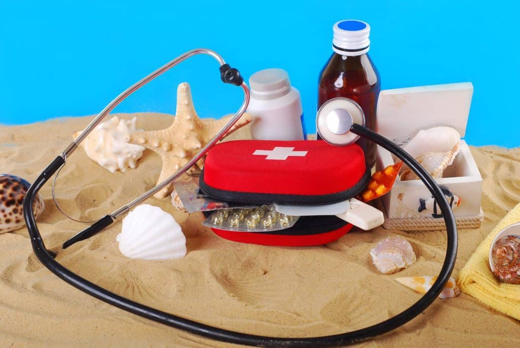 first aid box with medicines,thermometer and stethoscope on the beach as healthy travel tips