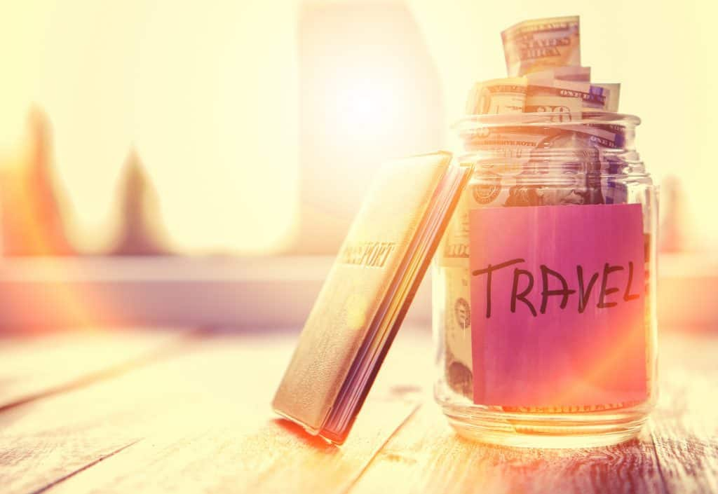 A glass jar with a note that says travel.  It is filled with money and has a passport leaning on it to show cruise vacation budget.